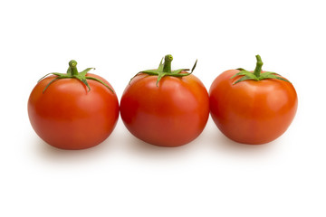 Three tomatoes in a row on white background