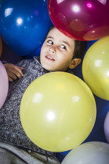 Play boy playing with balloons of many colors