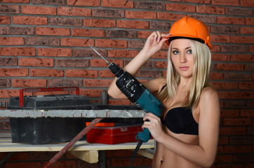 The woman in a building helmet with a drill in hands