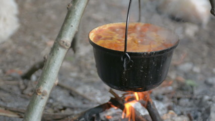 Goulash cooking on wood fire crane shot