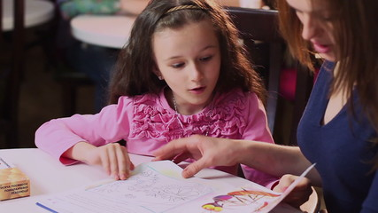 Mother shows happy little daughter color book, teaches colors