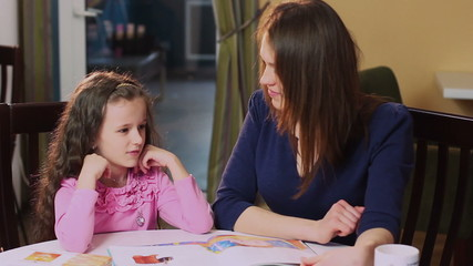 Woman mother teaching  little girl daughter, learning process