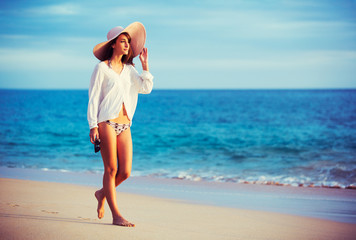 Beautiful young woman walking on tropical beach