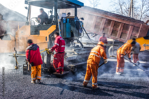 Leinwandbild Motiv Workers making asphalt with shovels at road constructio