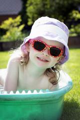 Little toddler bathing in the garden