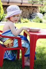 Little girl eating her lunch in the garden