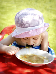 Little girl eating soup in the garden