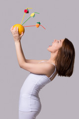 Beauty young woman keeps orange and drinks juice from one straw.
