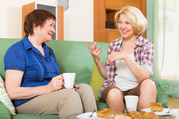 Two mature female  drinking tea