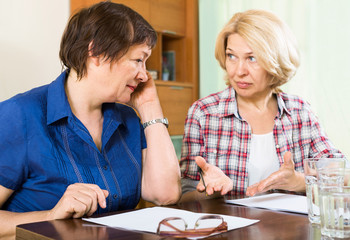 Two sad mature women with documents