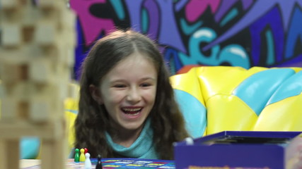 Excited girl playing board game, learning, listening, education