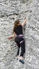 Young woman climbing difficult rock.