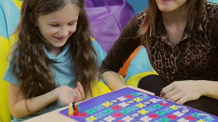 Woman playing board game smiling girl, mother teaching child