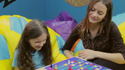 Girl teaches happy little sister, playing board game, having fun