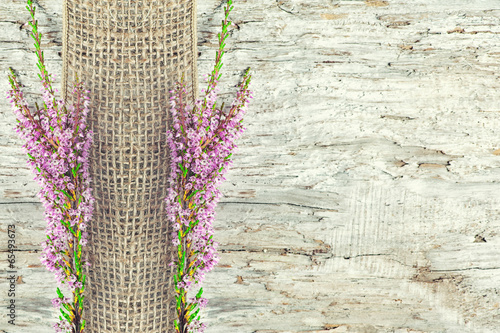 Old wooden background with heather and sacking ribbon