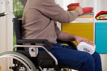 Disabled man sorting towels