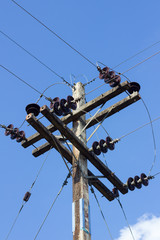 electrical post by the road with power line cables, against blue