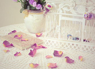 The book on a table with rose petals