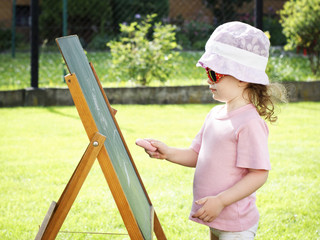 Little girl drawing on the board in the garden