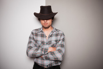 Young cowboy standing against dual colored background