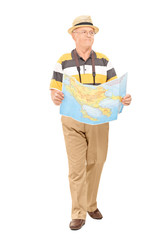 Mature tourist walking with map in his hands
