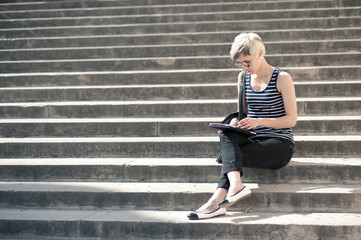 Young blonde woman using tablet while sitting on steps of Trocad