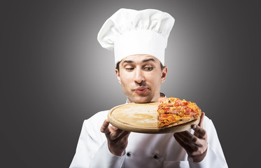 Humorous portrait of a man in chef's hat looking at pizza