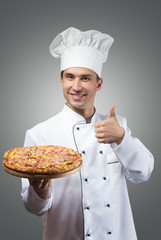 Smiling chef with fresh pizza showing thumbs up