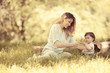 Mother and baby girl sitting and relaxing in nature.