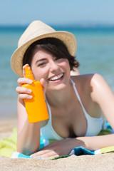 lachende junge frau mit sonnenschutz-spray