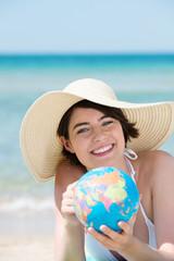 lächelnde frau am meer zeigt auf globus