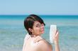 frau am strand benutzt sonnencreme