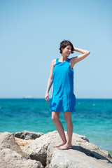 frau im blauen kleid genießt den urlaub am meer