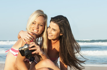 two attractive lesbian girls on the beach with film camera