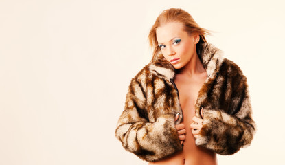 Portrait of attractive blond woman with fur with copy space.