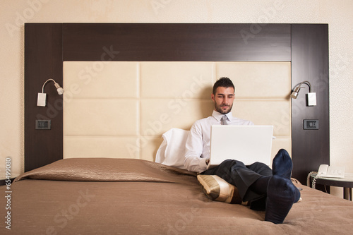 Young businessman working with computer sit on bed in hotel room
