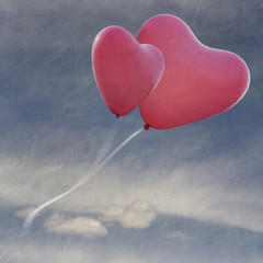 two balloons in the shape of heart flying in the sky with clouds