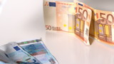 Euro notes dropping on white surface