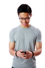 Cheerful asian man using smartphone on gray background