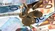 Euro coins dropping onto notes