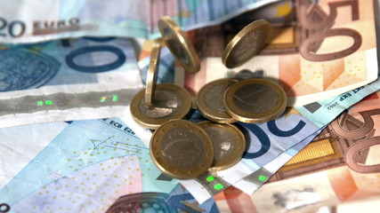 Euro coins dropping onto notes