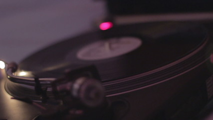 Hands of dj rotating vinyl record on turntable in nightclub