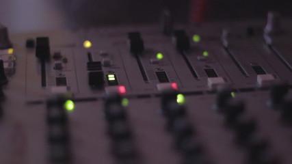 Dj's hands playing disco set, tweaking controls in nightclub