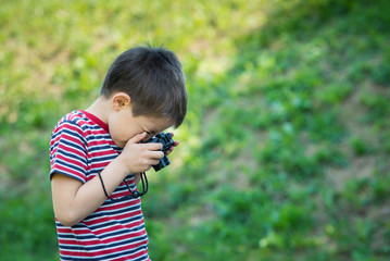 Portrait of child with digital compact camera outdoors.