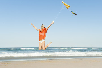 young attractive girl jumping with yellow kite on beach