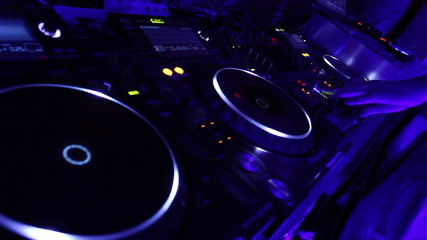 Dj spinning platter on turntable, tweaking controls on the deck