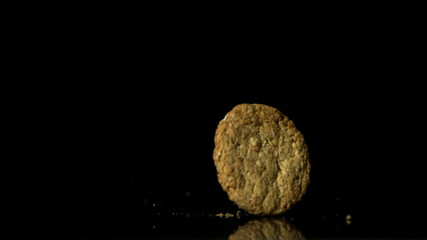 Biscuit falling on black surface