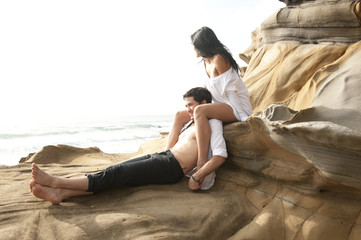 Young beautiful couple sharing a moment on beach rocks