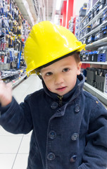 Boy pretending to be an engineer and shopping in a mechanical sh