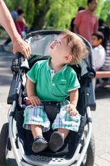 Close-up of a boy sitting in a baby carriage